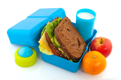 Healthy filled lunch box with whole meal bread vegetables and milk